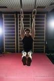 Homme bel de forme physique faisant l'exercice de plongement utilisant des anneaux dans le gymnase sport images libres de droits