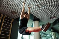 Homme bel de forme physique faisant l'exercice de plongement utilisant des anneaux dans le gymnase sport Images stock