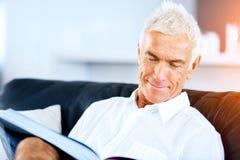 Homme bel de sennior lisant un livre détendant sur un sofa Photos libres de droits