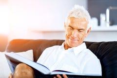 Homme bel de sennior lisant un livre détendant sur un sofa Images libres de droits