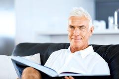 Homme bel de sennior lisant un livre détendant sur un sofa Photos stock