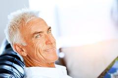Homme bel de sennior lisant un livre détendant sur un sofa Images stock