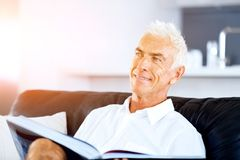 Homme bel de sennior lisant un livre détendant sur un sofa Photographie stock