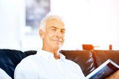 Homme bel de sennior lisant un livre détendant sur un sofa Photographie stock libre de droits