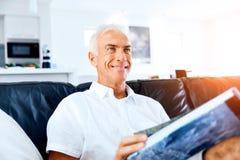 Homme bel de sennior lisant un livre détendant sur un sofa Photo libre de droits