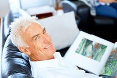 Homme bel de sennior lisant un livre détendant sur un sofa Photo stock