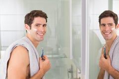 Homme bel de sourire avec la réflexion rasant dans la salle de bains Photo libre de droits