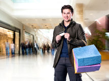Homme bel de sourire avec les paniers et la carte de crédit Photographie stock libre de droits