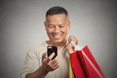 Homme bel de sourire tenant les paniers rouges regardant son smartphone image libre de droits