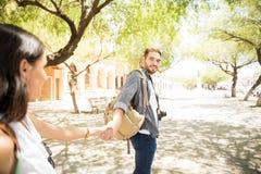 Homme bel de voyageur tenant la main du ` s de femme et la menant dessus Photographie stock libre de droits