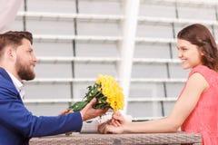 Homme bel donnant des fleurs à son amie Images libres de droits
