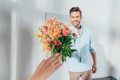 homme bel donnant le bouquet à son amie Images stock