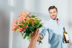 homme bel donnant le bouquet à son amie Photo stock