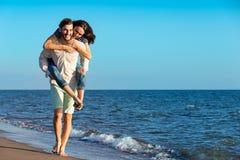 Homme bel donnant sur le dos à son amie à la plage Photo libre de droits