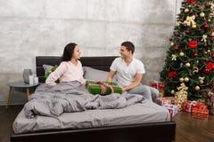 Homme bel donnant un présent à son épouse heureuse, tandis qu'elle hidin Image stock