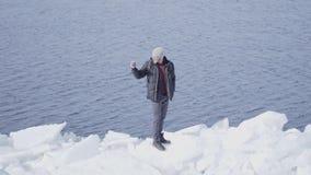 Homme bel en verres dans la position chaude de veste d'hiver sur le bloc de glace au glacier prenant la photo sur le téléphone po banque de vidéos