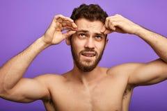Homme bel essayant de plumer ses sourcils photos libres de droits