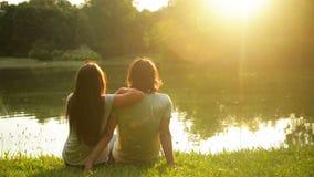 Homme bel et jolie femme regardant l'eau et le coucher du soleil de lac Vue arrière d'un beau couple romantique dehors banque de vidéos