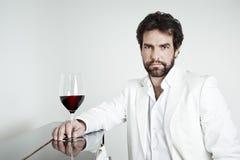 Homme bel et une glace de vin rouge Photographie stock
