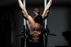 Homme bel exerçant son ABS au gymnase Photo stock