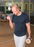 Homme bel faisant des enroulements de biceps Image stock