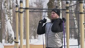 Homme bel faisant l'exercice de séance d'entraînement avec l'extenseur de forme physique sur l'au sol de sports photos stock