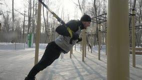 Homme bel faisant l'exercice de séance d'entraînement avec l'extenseur de forme physique sur l'au sol de sports image stock