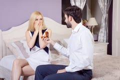 Homme bel faisant une proposition de mariage tout en offrant à son épouse une bague de fiançailles Image stock