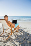 Homme bel focalisé travaillant sur son ordinateur portable Photo stock