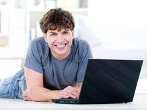 Homme bel heureux avec l'ordinateur portatif Image stock