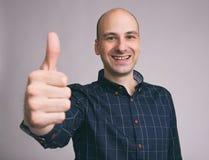 Homme bel heureux montrant des pouces  Images stock