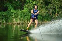 Homme bel heureux wakesurfing dans un lac photos libres de droits