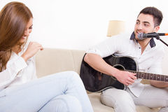 Homme bel jouant la guitare à la fille Photographie stock libre de droits