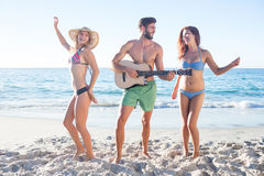 Homme bel jouant la guitare et sa danse d'amis Photos libres de droits