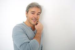 Homme bel mûr se penchant sur le mur Images stock