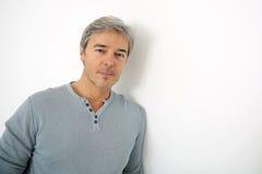 Homme bel mûr se penchant sur le mur blanc Images stock