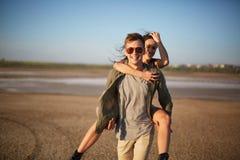 Homme bel marchant avec la jolie fille sur un dos sur un fond naturel Concept romantique de voyage Copiez l'espace Photos libres de droits
