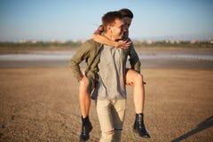 Homme bel marchant avec la jolie fille sur un dos sur un fond naturel Concept romantique de voyage Copiez l'espace Photo stock