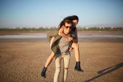 Homme bel marchant avec la jolie fille sur un dos sur un fond naturel Concept romantique de voyage Copiez l'espace Photographie stock