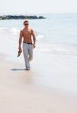 Homme bel marchant sur la plage Images libres de droits