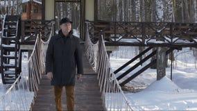 Homme bel marchant sur le pont décoratif dans le mouvement lent de parc de ville d'hiver banque de vidéos