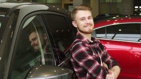 Homme bel montrant des pouces se penchant sur une nouvelle voiture au concessionnaire banque de vidéos