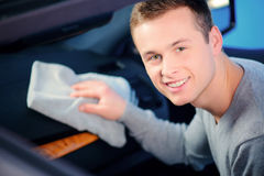 Homme bel nettoyant sa voiture Photographie stock