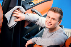 Homme bel nettoyant sa voiture Images stock