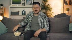 Homme bel observant le film effrayant à la TV mangeant du maïs éclaté cachant alors le visage clips vidéos