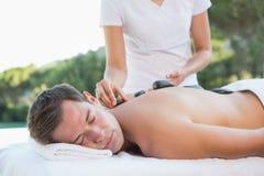 Homme bel obtenant un poolside en pierre chaud de massage photos stock