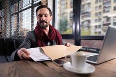 Homme bel optimiste mettant un calendrier dans l'enveloppe photographie stock libre de droits