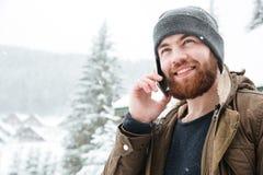 Homme bel parlant au téléphone portable dehors en hiver Photos libres de droits