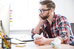 Homme bel pensant et papier de froissement sur son lieu de travail Images stock