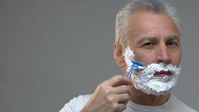 Homme bel plus âgé rasant attentivement sa barbe, procédure d'hygiène de matin banque de vidéos